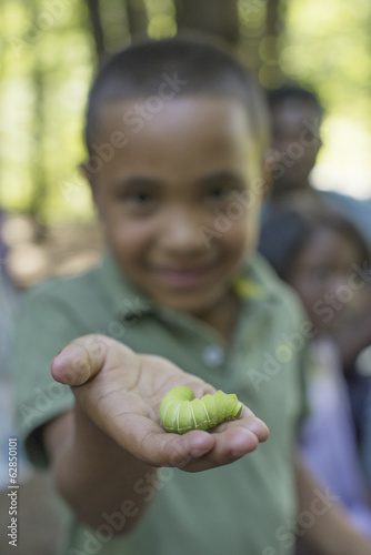 A family picnic meal in the shade of tall trees. A boy holding a fat green caterpillar.