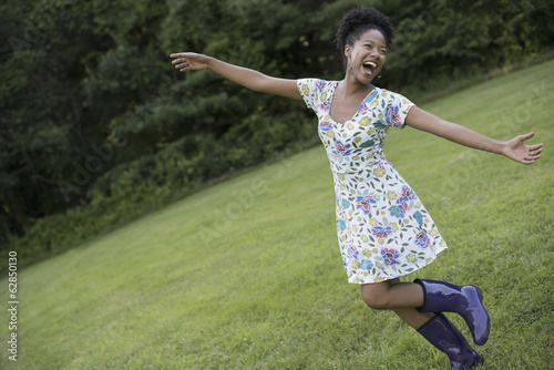 A young woman in a summer dress with her arms outstretched, celebrating freedom.