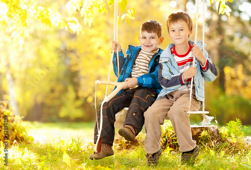 Happy boy on swing in autumn day