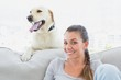 Happy woman posing with her yellow labrador on the couch
