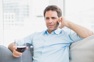 Cheerful man relaxing on sofa with glass of red wine talking