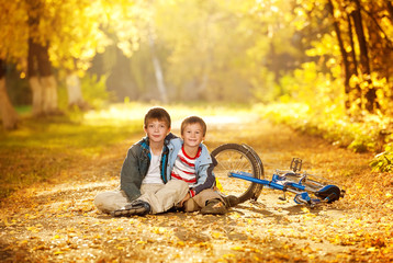 Two boys sitting in an alley with a bicycle autumn day
