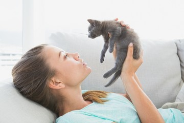 Cheerful woman lying on sofa holding a grey kitten