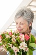 Retired woman smelling her bouquet of flowers
