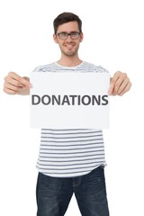 Portrait of a happy young man holding a donation note