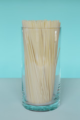 Uncooked organic pasta noodles in glass vase. Spaghetti noodles made of organic durum wheat semolina.