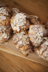 A group of fresh baked almond croissants, with icing sugar dusting. Organic party food desserts.