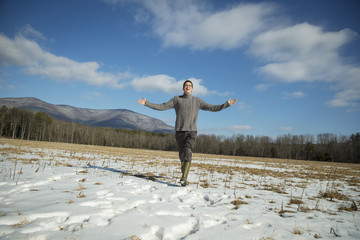 A man in a cable knit jumper and muck boots standing with his arms stretched out, in a snowy rural landscape.