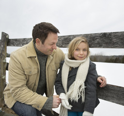 A man and a child leaning on a fence outdoors.  A farm in the snow.