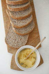 A wooden breadboard with a sliced brown loaf laid out. A dish of butter with a wooden butter knife.