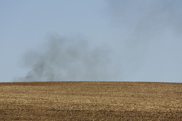 Smoke rising above a ridge, viewed across a ploughed field. Farmland near Pullman, Washington, USA
