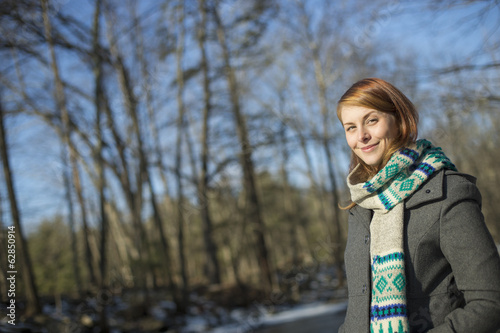 A young woman in a woodland on a winter day.  Wearing a bright knitted patterned scarf.