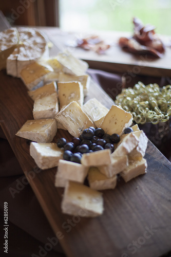 A wedding party meal.  A cheeseboard, with soft cheeses cut into triangles, and fresh fruits. Blueberries.