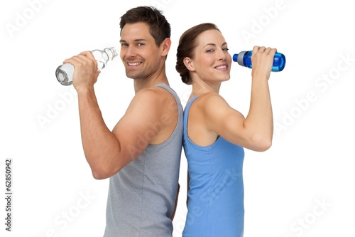 Happy fit young couple with water bottles
