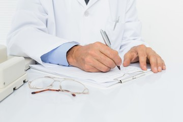 Mid section of a male doctor writing reports