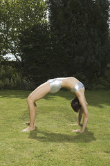 A young woman showing her flexibility, leaning backwards in an arch with hands and feet on grass
