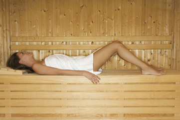 A wooden panelled sauna. A woman lying on a bench wrapped in a towel.