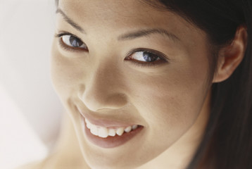 A young woman with brown eyes, smiling. Close up.
