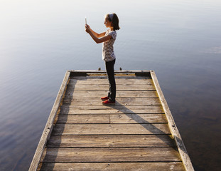 A young girl holding a digital tablet in front of her, standing on a wooden dock over the water.