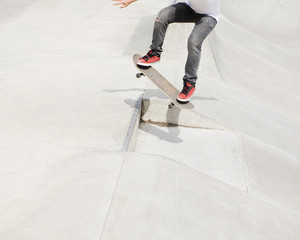 A teenage boy balancing on a skateboard in the city.
