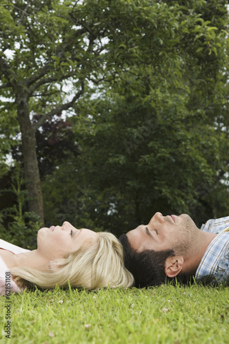 A couple lying on their backs, head touching on the grass,