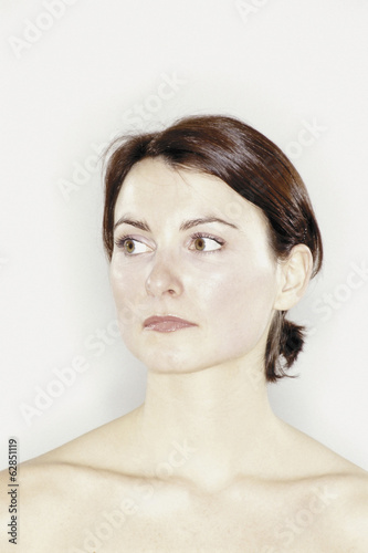 A studio portrait of a woman with brown hair tied back off her face.
