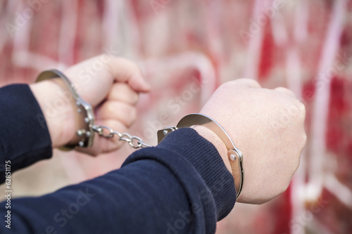 Man with outstretched arms in handcuffs near wall