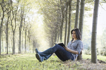 A woman sitting reading a book under the trees.