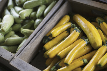 An organic farm stand. Boxes of yellow and green courgettes.