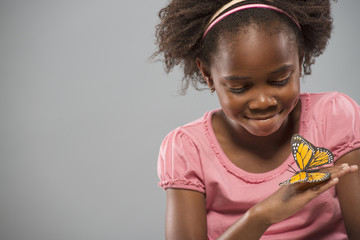 A girl with a yellow butterfly on her hand, sitting very still and concentrating.