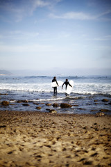 Two surfers at the water's edge inspecting the waves on Rockport Beach, USA