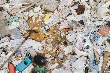 A heap of garbage and discarded items. Wooden plants, plastic and fabric, rubbish.