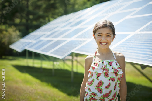 A child in the fresh open air on a sunny day, beside solar panels at a farm.