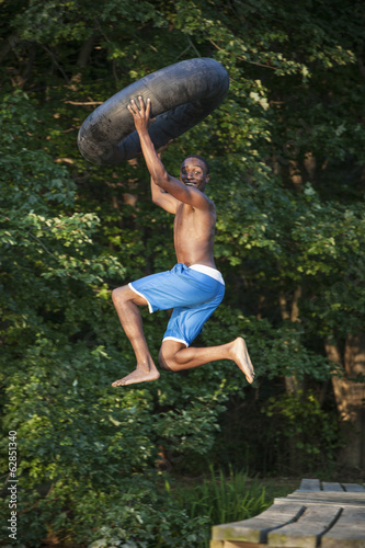A young person, boy holding a swim float tyre over his head and leaping into the water from the jetty.