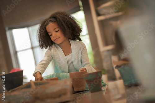 A young girl planting out seeds in clay pots.