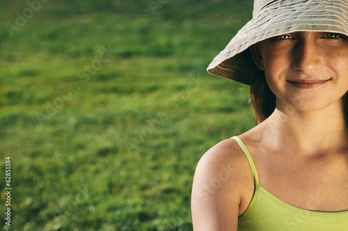 Portrait of smiling nine year old girl sitting on the grass
