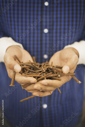 A person holding a heap of rusting metal nails taken from reclaimed timber.