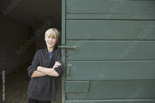 A boy leaning against a wooden barn door, at an animal sanctuary.