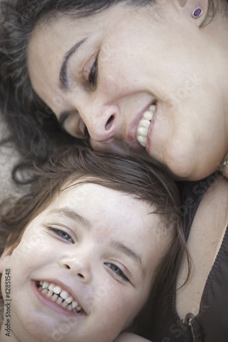 A close up of a mother and daughter lying with their heads together, smiling and laughing.