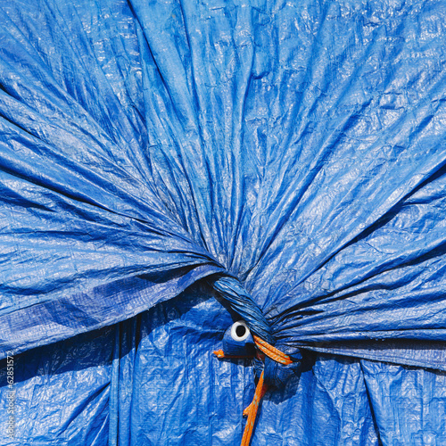 A blue tarpaulin, gathered and tied with rope as a covering over piles of commercial fishing nets, Fisherman's Terminal, Seattle