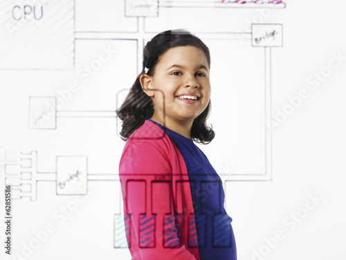 A young girl looking at a drawing of a computer motherboard circuit drawn on a see through clear surface.