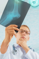 Doctor looks at x-ray image of knee joint