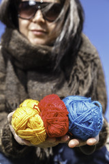 Young knitter with coloured yarns of wool
