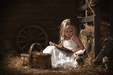 Girl with a kitten on hay