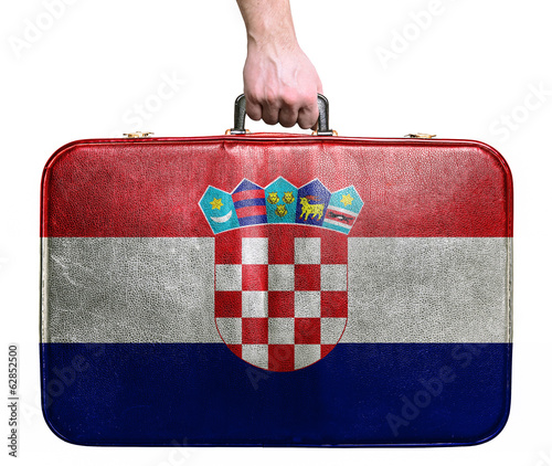 Tourist hand holding vintage leather travel bag with flag of Cro