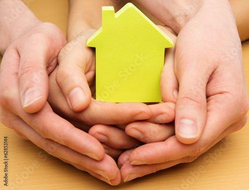 Man and woman hands holding conceptual paper house