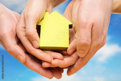 Hands holding conceptual paper house against