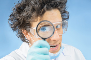 Mad doctor looks through a magnifying glass