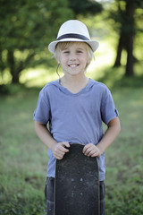 Cute smiling boy with skateboard outdoors, portrait