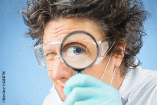 Crazy scientist looks through a magnifying glass